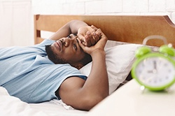 A young man lying awake in bed unable to go to sleep