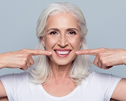 Senior woman pointing to natural looking denture