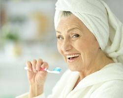 An older woman smiling while brushing her teeth