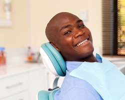 A young gentleman lying back in a dentist's chair smiling while waiting for the dentist to arrive