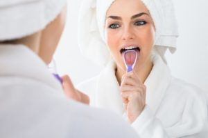 a woman cleaning her tongue with a tongue scraper