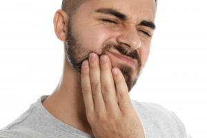 a younger man holding the side of his jaw and wincing in pain